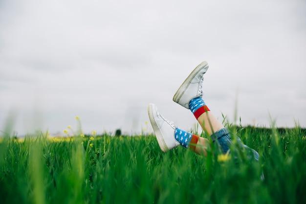 Piernas en zapatos blancos y hierba por encima