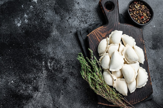 Pierogi de albóndigas crudas congeladas con patata sobre una tabla de madera. vista superior.
