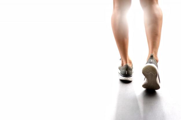 Pies de atleta corredor corriendo en carretera.