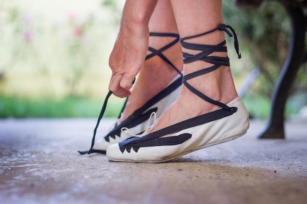 Pies de una bailarina atando sus zapatos