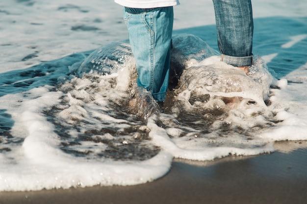 Pies de bebé y madre de pie en el mar