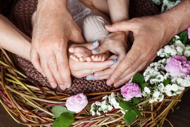 Pies de bebé en manos de los padres. los pies del pequeño bebé recién nacido en los padres en forma de manos de cerca. los padres y el niño. concepto de familia feliz.