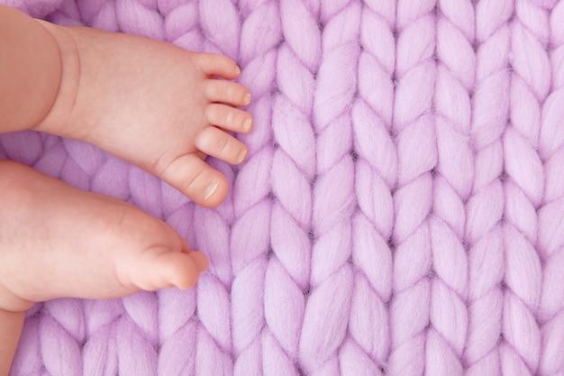 Pies de bebé sobre una gran manta de punto lila. tarjeta de felicitación para un baby shower, parto, embarazo. copyspace