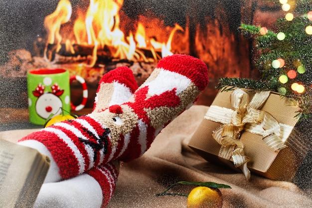 Pies en brillantes calcetines navideños junto a la chimenea