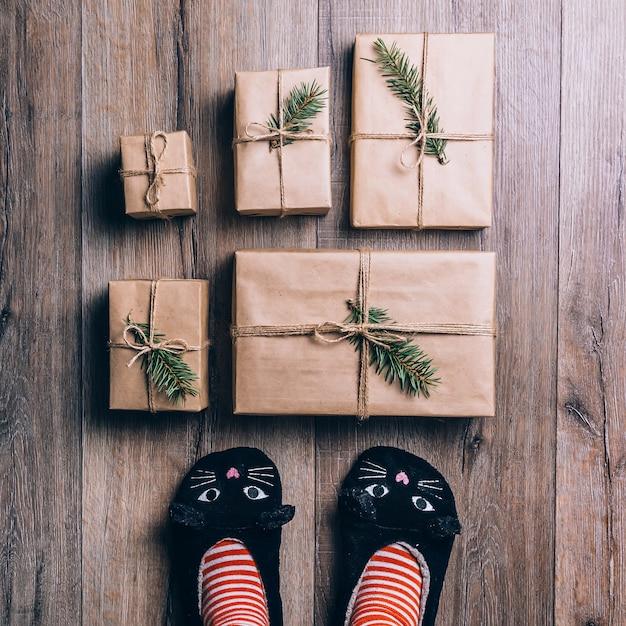 Pies con calcetines cálidos de invierno y zapatillas de gato frente a los regalos de navidad.