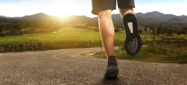 Pies de corredor corriendo en carretera closeup en zapato