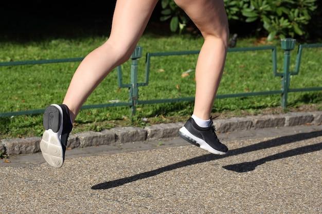 Pies corriendo atleta de distancia en el pavimento de piedra