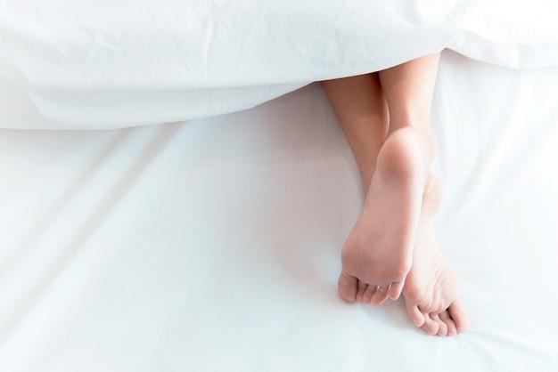 Pies de mujer en la cama debajo de la manta blanca. dormir y relajar el concepto