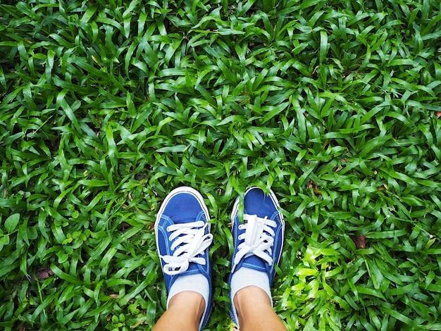 Pies de mujer selfie con zapatillas azules en la hierba verde