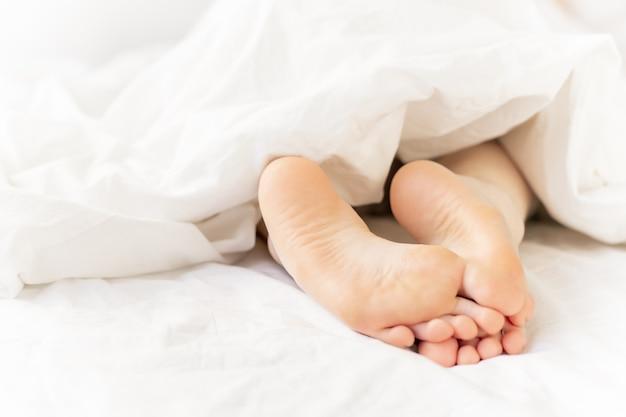 Pies descalzos en la cama
