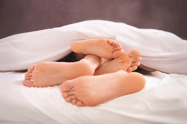 Pies descalzos humanos y edredón blanco