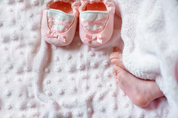 Pies descalzos de un lindo bebé recién nacido en una cálida manta blanca