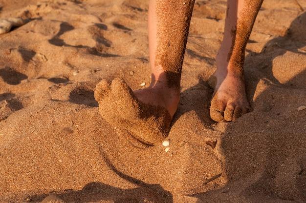 Pies descalzos de un niño en la arena de la playa