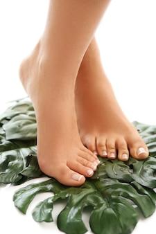 Pies descalzos sobre hojas. concepto de pedicura y cuidado de los pies