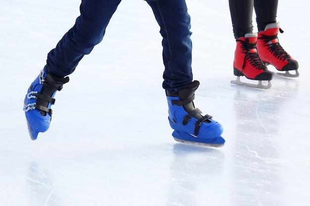 Pies de diferentes personas patinando en la pista de hielo.