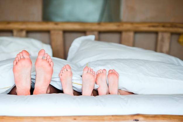Pies de familia en la cama