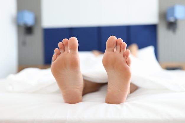 Pies femeninos acostados en la cama blanca debajo de las cubiertas de cerca. concepto de tratamiento de insomnio