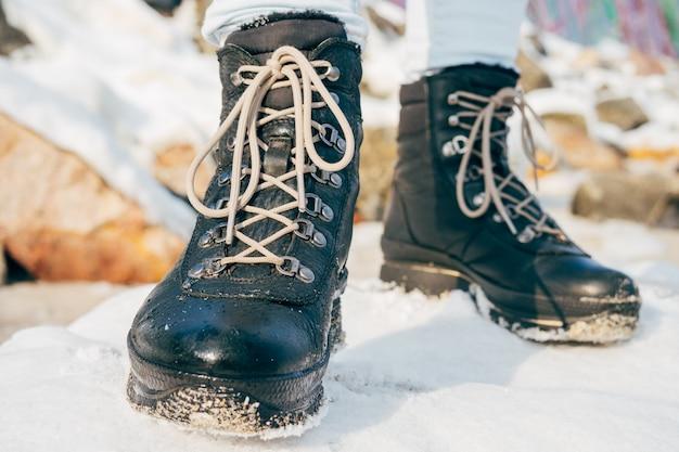 Pies femeninos en botas de invierno con cordones de pie en la nieve.