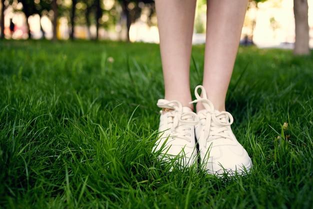 Pies femeninos en el césped caminar en el parque al aire libre