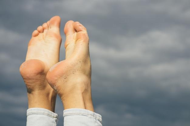 Pies femeninos descalzos en la arena de la playa sobre un fondo de cielo