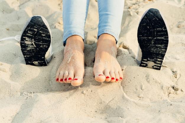 Pies femeninos desnudos en la arena al lado de los zapatos en la playa