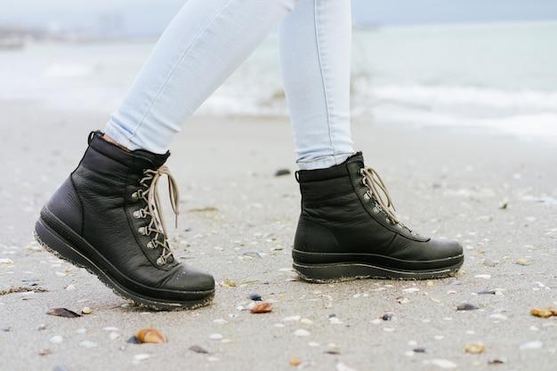 Los pies femeninos en jeans azules y botas negras de invierno están en la arena de la playa
