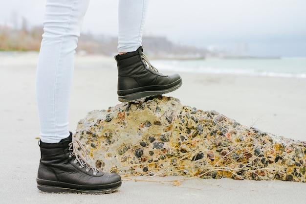 Pies femeninos en jeans y botas de invierno de pie sobre una piedra en la costa