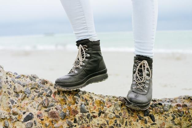 Pies femeninos en jeans y botas de invierno de pie sobre una piedra en el primer plano de la costa