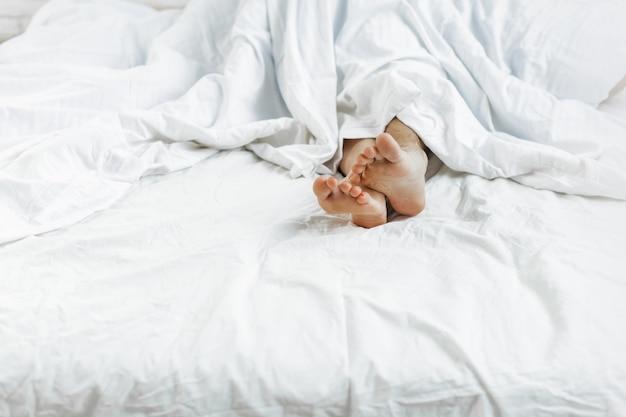 Pies femeninos y masculinos debajo de la sábana. concepto de sexo