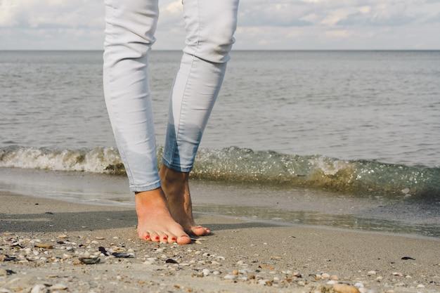 Pies femeninos en pantalones vaqueros descalzos caminar sobre el agua de mar en la playa