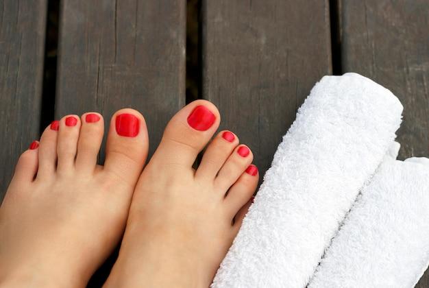 Pies femeninos con una pedicura roja en un piso de madera