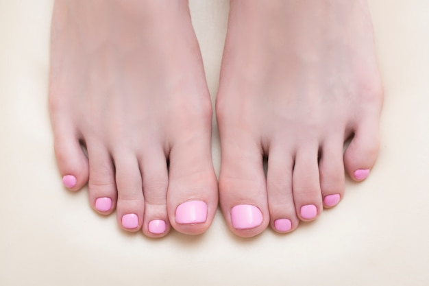 Pies femeninos con una pedicura rosa