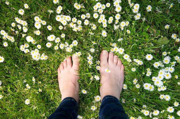 Pies femeninos de pie sobre la hierba verde y flores blancas