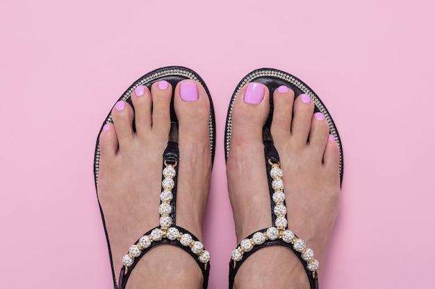Pies femeninos en sandalias