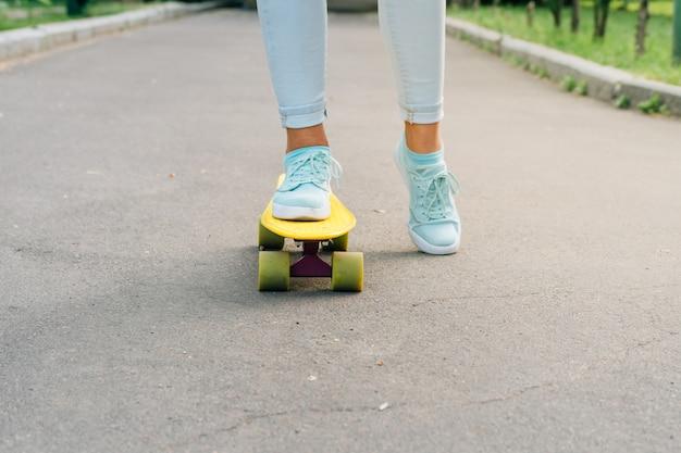 Pies femeninos en zapatillas de deporte montando un monopatín en asfalto