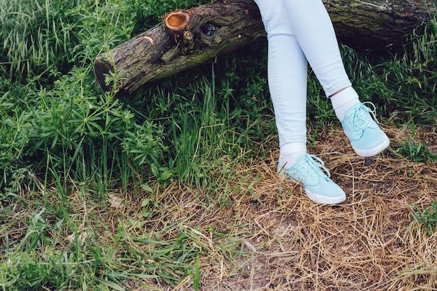 Pies femeninos en zapatillas y pantalones vaqueros en un registro en el bosque