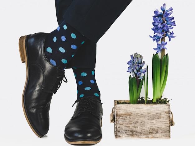 Pies de hombre, pantalón azul y calcetines brillantes.