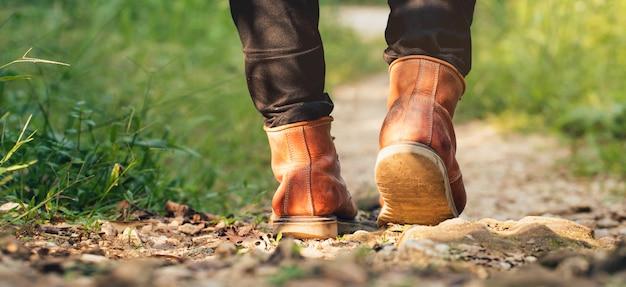Pies hombre senderismo al aire libre y bosque en el fondo Foto Premium