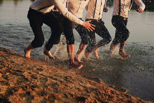 Pies de los hombres en el agua. los hombres corren sobre el agua. verano. grupo de feliz joven pies salpicaduras de agua