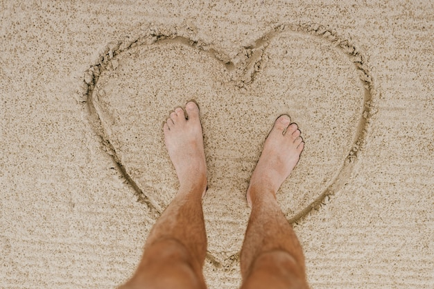 Pies de los hombres en el corazón en el fondo y arena clara.