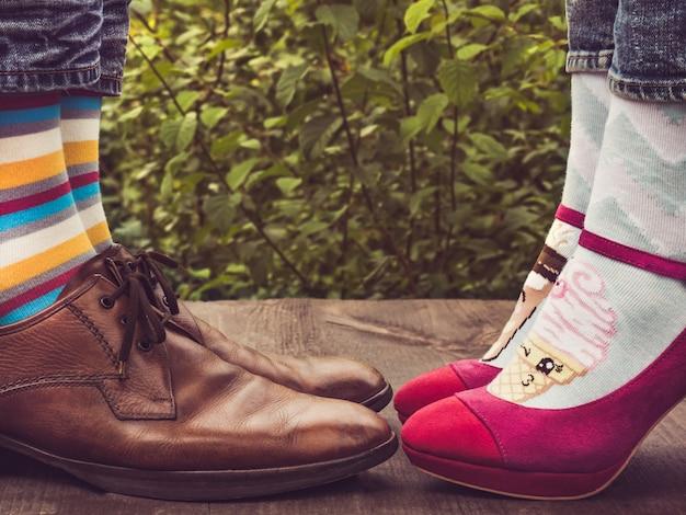 Pies de hombres y mujeres en zapatos elegantes, calcetines brillantes y coloridos.