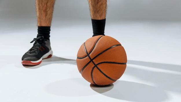 Los pies del joven jugando baloncesto