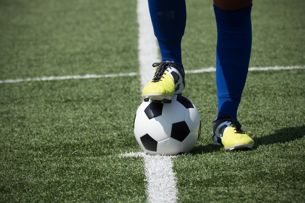 Los pies del jugador de fútbol sobre la pelota