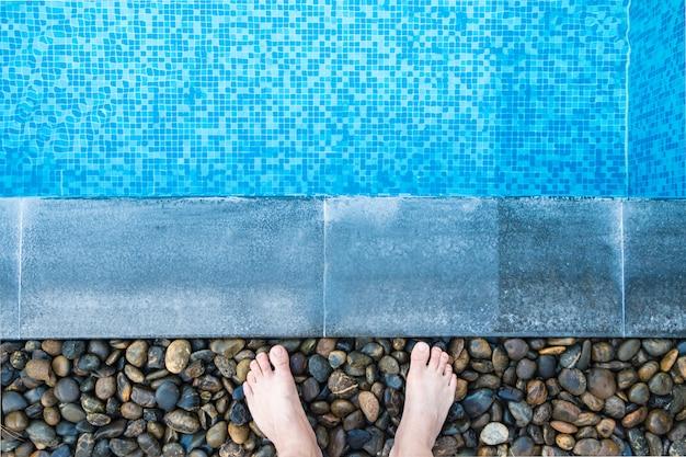 Pies en el lado de la piscina con azulejos de mosaico azul de la piscina.