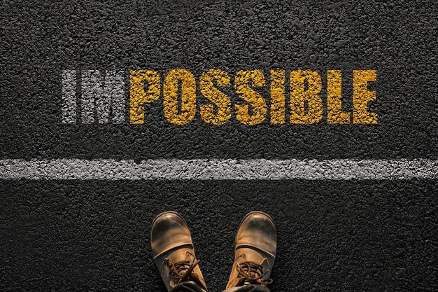 Los pies masculinos con botas se paran en el asfalto con una línea y el texto blanco es imposible con texto amarillo es posible, vista superior. el hombre y el texto creativo son posibles. ideas y oportunidades conceptuales