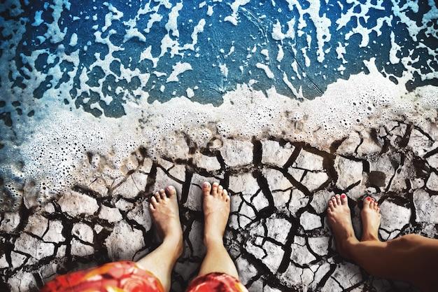 Los pies masculinos y femeninos están de pie sobre la tierra seca en la costa