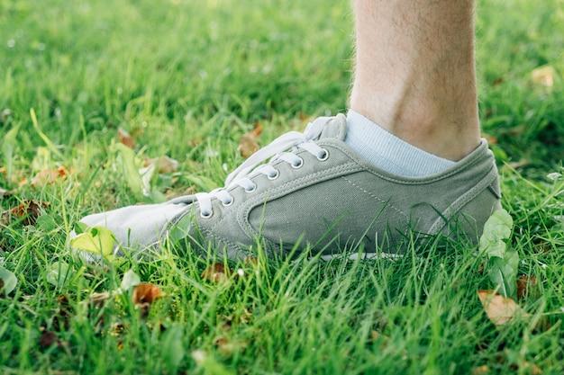 Pies masculinos en gumshoes gris sobre hierba