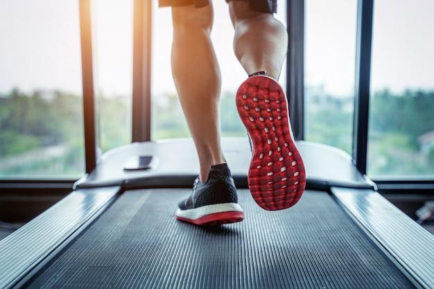 Pies masculinos en zapatillas corriendo en la cinta en el gimnasio. concepto de ejercicio.