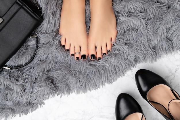 Pies de mujer con accesorios sobre fondo gris peludo. hermoso diseño clásico de uñas negras. manicura, concepto de salón de belleza de pedicura.