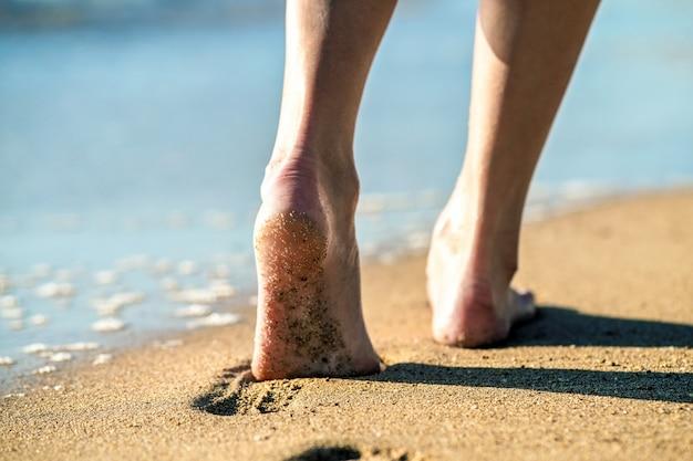 Pies de mujer caminando descalzo sobre la arena dejando huellas en la playa.